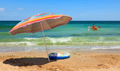 Beach umbrella and toy boat at sea — Stock Photo