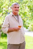 Senior man holding wine glass — Stock Photo