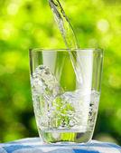 Doğa arka plan üzerine bir bardak su — Stok fotoğraf