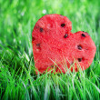 Watermelon heart on green grass. Valentine concept - Stock Photo