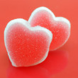 Sugar hearts on red background — Stock Photo