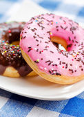 Fresh donuts on nature background — Stock Photo