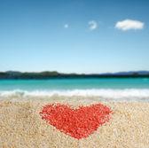 Czerwony znak serca na żółtym piasku. — Zdjęcie stockowe