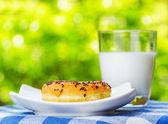 Färsk donut och glas mjölk på natur bakgrund — Stockfoto