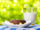 Donut fresco y vaso de leche en el fondo de la naturaleza — Foto de Stock