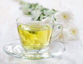 Cup of herbal tea and flowers — Stock Photo