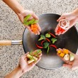Four hands puts fresh vegetables in the wok. Cooking concept — Stock Photo #22788760