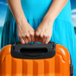 Woman in blue dress holds orange suitcase in hands on the beach - Lizenzfreies Foto