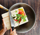 Fresh vegetables on the cutting board are falling in the wok. Co — Photo
