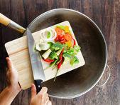 Kesme tahtası üzerinde taze sebze wok içinde düşer. co — Stok fotoğraf