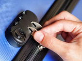 Woman locked her luggage in blue suitcase — Stock Photo