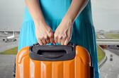 Donna in abito blu tiene la valigia arancia nelle mani su ba aeroporto — Foto Stock