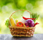 Fresh vegetables in the basket on wooden table — Stock Photo