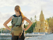 Young woman looking at golden pagoda. Hiking at Asia — Stock Photo