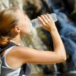 Young woman drinks water by waterfall - Stockfoto