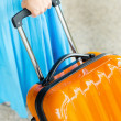 Woman in blue dress holds orange suitcase in hand — Stock Photo