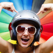 Funny girl in helmet having fun. Multicolored background — Stock Photo #24105215