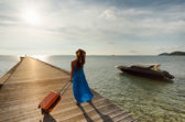 Young woman with suitcase on the pier — Stockfoto