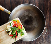 Fresh vegetables on the cutting board are falling in the wok. Co — Stock Photo