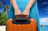 Woman in blue dress holds orange suitcase in hands on tropical l — Stock Photo