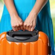 Woman in blue dress holds orange suitcase in hands on natural ba — Stock Photo #24179847