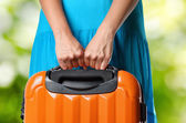 Woman in blue dress holds orange suitcase in hands on natural ba — Stockfoto