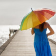 Young woman walking on the pier with umbrella — Stock Photo #25556917