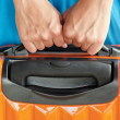 Woman in blue dress holds orange suitcase in hands — Stock Photo #25556923