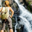 Female hiker looking at waterfall — Stock Photo #25557039