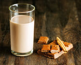 Chocolate milk with chocolate and cinnamon on dark wooden table — Stock Photo