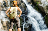 Female hiker looking at waterfall — Photo
