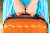 Mujer con vestido azul tiene maleta naranja en manos — Foto de Stock