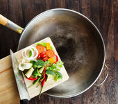 Legumes frescos numa tábua estão caindo no wok. co — Fotografia Stock