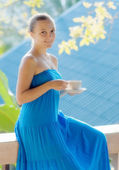 Young woman drinking coffee on morning terrace — Stock Photo
