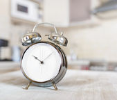 Alarm clock on a table in the kitchen — Stock Photo