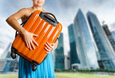 Woman in blue dress holds orange suitcase in hands — Stock Photo