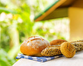 Fresh bread and checkered napkin on wooden table on rural backgr — Stock Photo