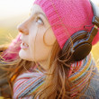 Young woman enjoying a music in the fall season. Autumn outdoor — Stock Photo