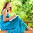Young woman writing to notebook. Outdoor portrait — Foto Stock