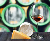 Glass of wine and cheese in winery — ストック写真