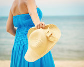 Woman in blue dress throws hat on the beach — Stock Photo