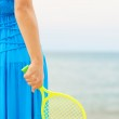 Woman in blue dress playing tennis on the beach — Stock Photo #33213633