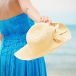 Woman in blue dress throws hat on the beach — Stock Photo #33213635