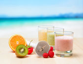 Fruit smoothie on wooden table on tropical beach — Stock Photo
