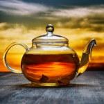Teapot of fresh tea on sky background — Stock Photo #33444691