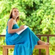 Stock Photo: Young woman writing to notebook. Outdoor portrait