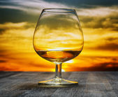 Glass of brandy on evening sky background — Stock Photo