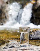 Glass of water by waterfall — Stock Photo