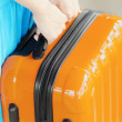 Woman in blue dress holds orange suitcase in hands — 图库照片