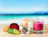 Vegetable smoothie on wooden table on the beach background — Stock Photo